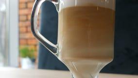 Ο καφές latte αναμιγνύεται με το κουτάλι Αναμιγνύοντας τον καφέ με το γάλα κοντά επάνω δείτε απόθεμα βίντεο