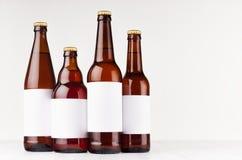 Ο καφετής διαφορετικός τύπος συλλογής μπουκαλιών μπύρας με την κενή άσπρη ετικέτα στο λευκό ξύλινο πίνακα, χλευάζει επάνω Στοκ Εικόνες