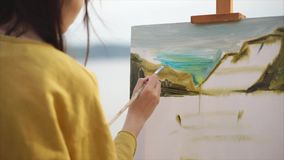 Ο καλλιτέχνης γυναικών χρωματίζει μια ελαιογραφία στον καμβά, ο οποίος στέκεται easel απόθεμα βίντεο