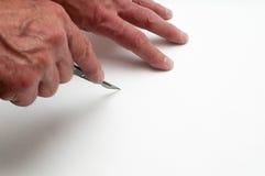 Ο καλλιτέχνης επανδρώνει την κοπή χεριών με ένα χειρουργικό νυστέρι Στοκ εικόνες με δικαίωμα ελεύθερης χρήσης