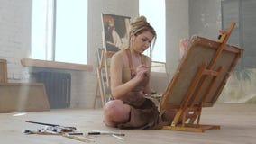 Ο καλλιτέχνης επισύρει την προσοχή τη συνεδρίαση εικόνων στο πάτωμα, πλάγια όψη κίνηση αργή φιλμ μικρού μήκους