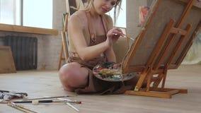 Ο καλλιτέχνης επισύρει την προσοχή τη συνεδρίαση εικόνων στο πάτωμα, σε αργή κίνηση Πλάγια όψη απόθεμα βίντεο