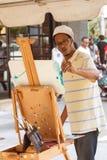 Ο καλλιτέχνης εφαρμόζει τα κτυπήματα βουρτσών στη ζωγραφική στο φεστιβάλ τεχνών Στοκ εικόνες με δικαίωμα ελεύθερης χρήσης