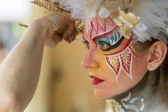 Ο καλλιτέχνης εφαρμόζει το χρώμα σώματος στο πρόσωπο του θηλυκού προτύπου Στοκ Εικόνες
