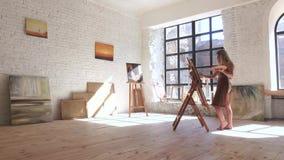Ο καλλιτέχνης δημιουργεί το αριστούργημά της στο μεγάλο φωτεινό στούντιο τέχνης, εργαστήριο απόθεμα βίντεο
