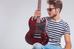Ο καλλιτέχνης θέτει στο στούντιο κοιτάζοντας μακριά με την κιθάρα διαθέσιμη, στο γόνατο, Στοκ φωτογραφίες με δικαίωμα ελεύθερης χρήσης