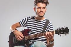 Ο καλλιτέχνης θέτει στο στούντιο που κάθεται παίζοντας την κιθάρα και aw Στοκ φωτογραφία με δικαίωμα ελεύθερης χρήσης