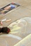 Ο καλλιτέχνης κιμωλίας σκιαγραφεί το πορτρέτο επάνω στο πεζοδρόμιο Στοκ Φωτογραφίες