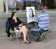 Ο καλλιτέχνης οδών επισύρει την προσοχή ένα κορίτσι στο Arbat Στοκ φωτογραφίες με δικαίωμα ελεύθερης χρήσης