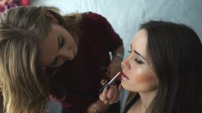 Ο καλλιτέχνης σύνθεσης κάνει ένα κορίτσι το όμορφο makeup για τα χείλια πριν από ένα σημαντικό γεγονός απόθεμα βίντεο