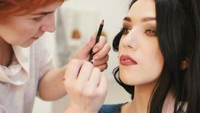 Ο καλλιτέχνης σύνθεσης κάνει τη σύνθεση τα νέα χείλια γυναικών με το χειλικό μολύβι για να κτυπήσει τα χείλια απόθεμα βίντεο