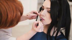 Ο καλλιτέχνης σύνθεσης κάνει τη σύνθεση τα νέα χείλια γυναικών με το χειλικό μολύβι για να κτυπήσει τα χείλια φιλμ μικρού μήκους