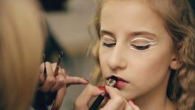 Ο καλλιτέχνης σύνθεσης κάνει το νέο κορίτσι ηθοποιών το όμορφο makeup για τα χείλια πριν από την απόδοση χορού στο εσωτερικό απόθεμα βίντεο