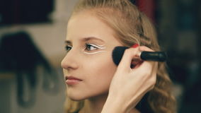 Ο καλλιτέχνης σύνθεσης κάνει το νέο κορίτσι ηθοποιών το όμορφο makeup για το πρόσωπο πριν από την απόδοση χορού στο εσωτερικό απόθεμα βίντεο
