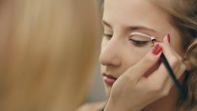 Ο καλλιτέχνης σύνθεσης κάνει το νέο κορίτσι ηθοποιών το όμορφο makeup για τα μάτια πριν από την απόδοση χορού στο εσωτερικό φιλμ μικρού μήκους