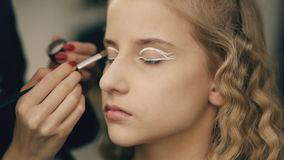 Ο καλλιτέχνης σύνθεσης κάνει το νέο κορίτσι ηθοποιών το όμορφο makeup για τα μάτια πριν από την απόδοση χορού στο εσωτερικό απόθεμα βίντεο