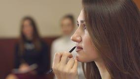 Ο καλλιτέχνης σύνθεσης χρωματίζει τα χείλια σε ένα νέο κορίτσι απόθεμα βίντεο