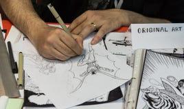 Ο καλλιτέχνης σύρει μια ιστορία σε σκίτσα Στοκ φωτογραφίες με δικαίωμα ελεύθερης χρήσης