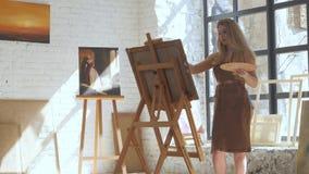 Ο καλλιτέχνης χρωματίζει την εικόνα στον καμβά με τα ελαιοχρώματα στο εργαστήριο απόθεμα βίντεο