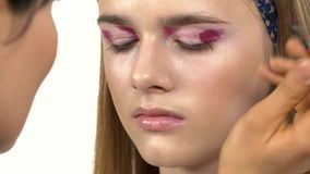 Ο καλλιτέχνης Makeup ισχύει αποζημιώνει το κορίτσι, σκιά ματιών απόθεμα βίντεο