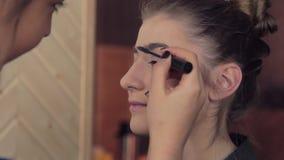 Ο καλλιτέχνης Makeup ισχύει makeup στο πρότυπο brow φιλμ μικρού μήκους