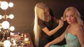 Ο καλλιτέχνης Makeup κάνει ένα κορίτσι το όμορφο makeup πριν από ένα σημαντικό γεγονός η γυναίκα που εφαρμόζει το καλλυντικό με μ απόθεμα βίντεο