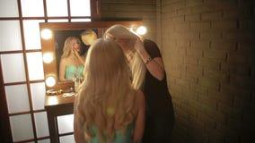 Ο καλλιτέχνης Makeup κάνει ένα κορίτσι το όμορφο makeup πριν από ένα σημαντικό γεγονός η γυναίκα που εφαρμόζει το καλλυντικό με μ φιλμ μικρού μήκους