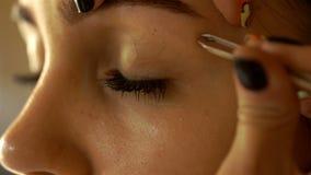 Ο καλλιτέχνης Makeup ρυθμίζει το νέο κορίτσι φρυδιών με τα τσιμπιδάκια απόθεμα βίντεο