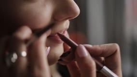 Ο καλλιτέχνης Makeup χρωματίζει τα χείλια για το κορίτσι Επαγγελματική σύνθεση του προτύπου Όμορφη νύφη ` s makeup φιλμ μικρού μήκους