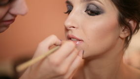 Ο καλλιτέχνης Makeup χρωματίζει τα χείλια της απόθεμα βίντεο