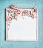 Ο κενός άσπρος πίνακας κιμωλίας και τα όμορφα λουλούδια χρώματος κρητιδογραφιών συσσωρεύουν στο τυρκουάζ shabby κομψό υπόβαθρο, τ Στοκ φωτογραφία με δικαίωμα ελεύθερης χρήσης