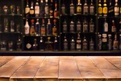Ο κενός ξύλινος μετρητής φραγμών με το υπόβαθρο και τα μπουκάλια του εστιατορίου στοκ φωτογραφία με δικαίωμα ελεύθερης χρήσης