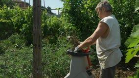 Ο κηπουρός η χρησιμοποίηση του καταστροφέα εγγράφων κλάδων Παραγωγή του πριονιδιού απόθεμα βίντεο
