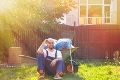 Ο κηπουρός κάθεται στη χλόη, που κλίνει σε ένα κάρρο με τα εργαλεία Ηλιοφάνεια από τη δεξιά πλευρά Έντονο φως ήλιων στοκ εικόνες