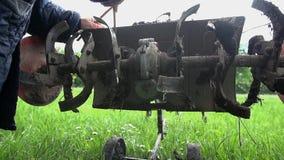 Ο κηπουρός κολλά το στενόμακρο ξύλινο ραβδί στο άροτρο για να καθαρίσει το ρύπο απόθεμα βίντεο