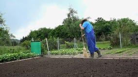 Ο κηπουρός σκουπίζει το πάτωμα στον κήπο του φιλμ μικρού μήκους