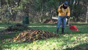 Ο κηπουρός στα θερμά ενδύματα προετοιμάζει το λίπασμα μορφής φύλλων φθινοπώρου στο κατώφλι 4K φιλμ μικρού μήκους