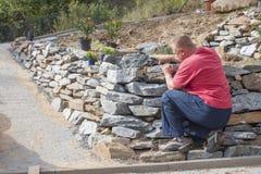 Ο κηπουρός χτίζει έναν τοίχο πετρών, ο αρχιτέκτονας προτείνει τις προμήθειες Στοκ Φωτογραφία