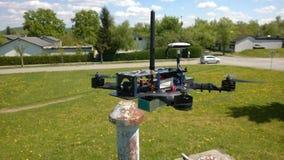 Ο κηφήνας αγώνα που αιωρείται 1m επάνω από την επίγεια πτήση παρατηρεί την αβούρτσιστη μηχανή geolocation Στοκ Εικόνα