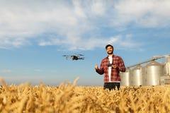 Ο κηφήνας αιωρείται μπροστά από τον αγρότη με το μακρινό ελεγκτή στα χέρια κοντά στη σιταποθήκη Το Quadcopter πετά κοντά σε πειρα Στοκ Εικόνες