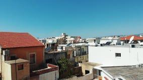 Ο κηφήνας ανεβαίνει στα paphos πόλεων της Κύπρου με το πορτοκαλί δέντρο μπροστά και τα κτήρια πόλεων με τις κόκκινες στέγες ( απόθεμα βίντεο