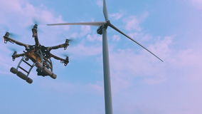 Drone takes off from the hands of a girl near a wind turbine, slow motion. Stock Footage
