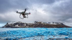 Ο κηφήνας με μια κάμερα πετά στο παγόβουνο στοκ φωτογραφίες με δικαίωμα ελεύθερης χρήσης