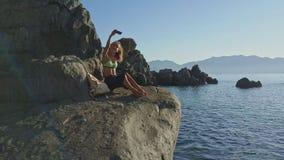 Ο κηφήνας περιστρέφεται γύρω από το κορίτσι που παίρνει τις φωτογραφίες ενάντια στη θάλασσα ήλιων αύξησης φιλμ μικρού μήκους