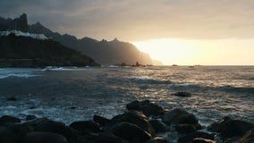 Ο κηφήνας πετά πέρα από τα ωκεάνια κύματα που συντρίβουν στους βράχους και που ψεκάζουν στο όμορφο φως ηλιοβασιλέματος στην παραλ απόθεμα βίντεο