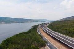 Ο κηφήνας πυροβόλησε το εναέριο τοπίο άποψης των κατώτερων φόρων αυτοκινητόδρομων κατασκευής κοντά στο μεγάλο φυσικό ποταμό στοκ φωτογραφία