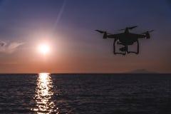 Ο κηφήνας στον ουρανό ηλιοβασιλέματος τα ωκεάνια βουνά κυμάτων κλείνουν επάνω του quadrocopter υπαίθρια έννοια για γαμήλιο videog στοκ φωτογραφία
