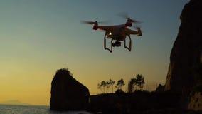 Ο κηφήνας στον ουρανό ηλιοβασιλέματος τα ωκεάνια βουνά κυμάτων κλείνουν επάνω του quadrocopter υπαίθρια έννοια για γαμήλιο videog απόθεμα βίντεο