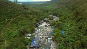 Ο κηφήνας χαμηλώνει στον ποταμό που τρέχει μεταξύ των δύσκολων τραπεζών με τα σπίτια απόθεμα βίντεο