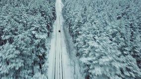 Ο κηφήνας χαράζει με υψηλή ταχύτητα το αυτοκίνητο στη χιονώδη εθνική οδό στα κομψά δασικά, κινηματογραφικά πλαίσια απόθεμα βίντεο